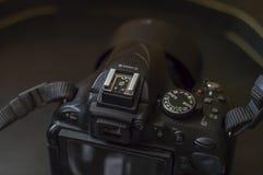 Digital kamera som ligger på en mörk tabell royaltyfri fotografi