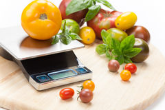 Digital Kitchen Scale. On table surrounded with fresh tomatoes, and basil Royalty Free Stock Photo