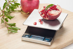 Digital Kitchen Scale. On table and pomegranate Stock Images