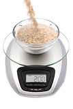 Digital kitchen scale with bowl of oat bran Royalty Free Stock Photography