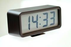 Digital klocka på den vita tabellen arkivfoton