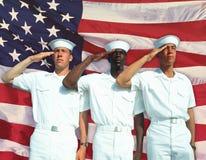 Digital komposit: Etniskt olika amerikanska sjömän och amerikanska flaggan Arkivbilder