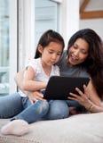 digital lycklig modertablet för dotter Arkivbild