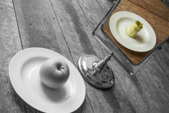 Digital Art opposites. A digital manipulation of opposites. The apple is whole and in black and white but the reflection shows an eaten apple and in colour royalty free stock image