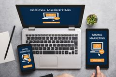 Digital marketing concept on laptop, tablet and smartphone screen. Over gray table. Flat lay stock images