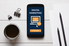 Digital marketing concept on smart phone screen. With office objects on white wooden table. Flat lay royalty free stock photo