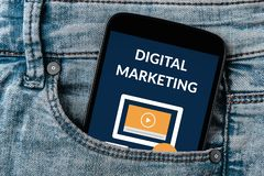 Digital marketing concept on smartphone screen. In jeans pocket. Flat lay stock photo