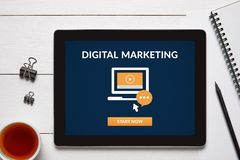 Digital marketing concept on tablet screen. With office objects on white wooden table. All screen content is designed by me. Flat lay stock image