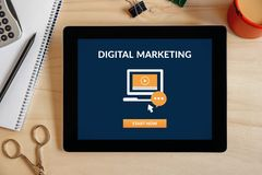 Digital marketing concept on tablet screen. With office objects on wooden desk. Top view stock photos