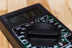 Digital measuring multimeter on wooden floor. It shows 4.33V or fully charged battery. Includes voltmeter, ampermeter, ohmmeter royalty free stock photo