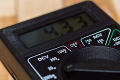 Digital mesurant le multimètre sur le plancher en bois Il montre 4 33V ou batterie entièrement chargée Inclut le voltmètre, amper photographie stock libre de droits
