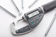 Digital micrometer with adjustable pressure measurement with steel screws on white background. Measurement of details in the bolts and nuts industry. Measuring stock photography