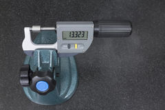 Digital micrometer measurement a pivot bearing probe. On granite table Stock Image