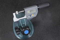 Digital micrometer measurement a pivot bearing probe. On granite table Stock Photo