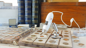 Digital microscope on album with coins from different countries Stock Images