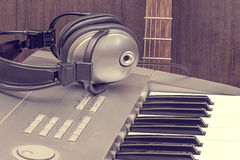 Digital midi keyboard, headphones and acoustic guitar. Royalty Free Stock Photo