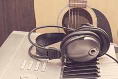 Digital midi keyboard, headphones and acoustic guitar. Stock Image