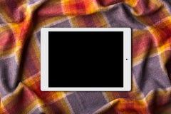 Digital minnestavla med den tomma skärmen på den varma sängöverkastet Kall vinter för utgifter hemma med den moderna grejen Moder royaltyfri fotografi