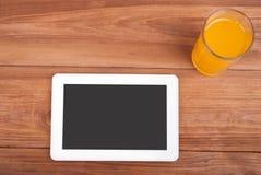 Digital minnestavla och ett exponeringsglas av orange fruktsaft Arkivfoton