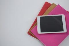 Digital minnestavla på bokbunt på vit bakgrund Royaltyfria Bilder