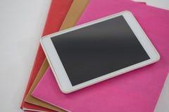 Digital minnestavla på bokbunt på vit bakgrund Arkivfoto