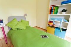 Digital minnestavla på säng i barnsovrum Royaltyfri Fotografi