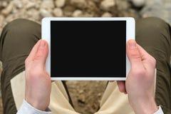 Digital minnestavladator med skärmen i manliga händer över kafébakgrund - tabell, kopp kaffe royaltyfria bilder
