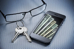 Digital Money Wallet Cell Phone. A cell phone with American money that is a digital wallet or e-wallet with keys and glasses on a desk surface Royalty Free Stock Photography