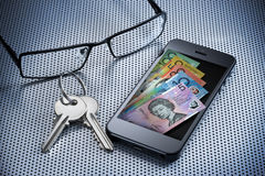 Digital Money Wallet Mobile Phone. A cell phone with australian money that is a digital wallet or e-wallet with keys and glasses on a desk surface Royalty Free Stock Photo