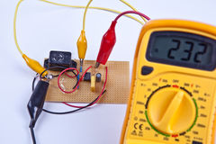 Digital multimeter with board. Digital multimeter with circuit board in background stock image