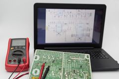Circuit board with Electrical diagrams by laptop. stock photography