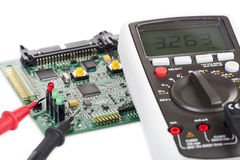 Digital multimeter and a circuit board Stock Photos
