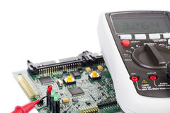 Digital multimeter and a circuit board Stock Images