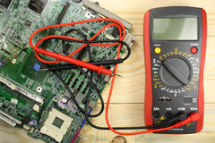 Digital multimeter with circuit board on a wooden table Stock Image