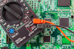 Digital multimeter with connected probes on a green printed circuit board Royalty Free Stock Image