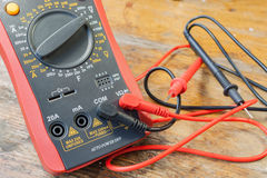 Digital multimeter with the connected probes on a table in a workshop Royalty Free Stock Image