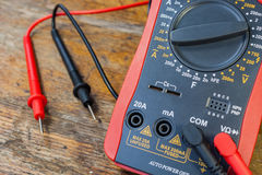 Digital multimeter with the connected probes on a table in a workshop Royalty Free Stock Photography