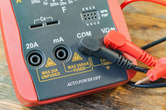 Digital multimeter with the connected probes on a table in a workshop Royalty Free Stock Images
