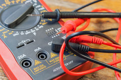 Digital multimeter with the connected probes on a table in a workshop Royalty Free Stock Photo