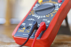 Digital multimeter with connected probes on a wooden table Stock Photography