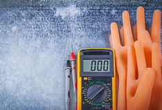 Digital multimeter dielectric rubber gloves on metallic backgrou Stock Photography