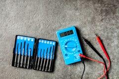 Digital multimeter on grey background. Digital multimeter and precision screwdriver set Royalty Free Stock Photography