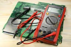 Digital multimeter med strömkretsbrädet på en trätabell arkivfoton