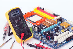 Digital Multimeter and motherboard Stock Image