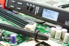 Digital multimeter pen type on the motherboard in a workshop Stock Images