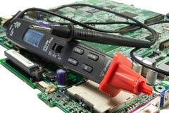 Digital multimeter pen type on the motherboard in a workshop Royalty Free Stock Image