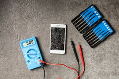 Digital multimeter on grey background. Digital multimeter and precision screwdriver set Stock Photo
