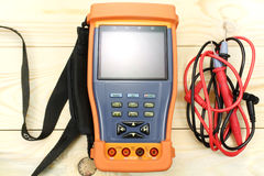 Digital multimeter with probe on a wooden table stock images