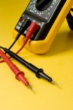 Digital multimeter probes. On yellow surface Royalty Free Stock Photo