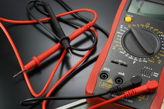 Digital multimeter with probes on a black background Stock Image